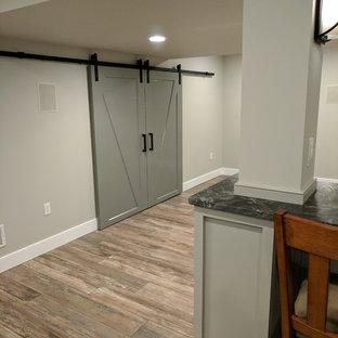 Réalisation d'un sous-sol tradition semi-enterré et de taille moyenne avec un mur gris et un sol en carrelage de porcelaine.