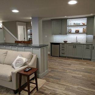 Modelo de sótano con ventanas tradicional renovado, de tamaño medio, con paredes grises y suelo de baldosas de porcelana