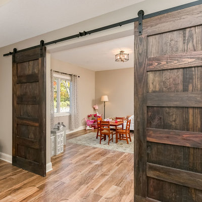 Inspiration for a mid-sized rustic walk-out medium tone wood floor and brown floor basement remodel in Minneapolis with beige walls, a two-sided fireplace and a stone fireplace