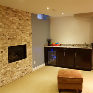 Inspiration for a mid-sized timeless underground carpeted basement remodel in Toronto with beige walls, a standard fireplace and a stone fireplace