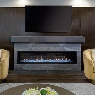 Inspiration pour un sous-sol design semi-enterré et de taille moyenne avec un mur gris, un sol en bois foncé, une cheminée ribbon, un manteau de cheminée en béton et un sol marron.