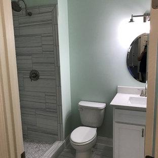 Inspiration pour un petit sous-sol traditionnel avec un mur vert, un sol en carrelage de céramique et un sol gris.