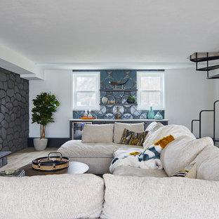 Aménagement d'un sous-sol rétro semi-enterré avec un mur blanc, un sol en bois clair, une cheminée standard et un manteau de cheminée en pierre.