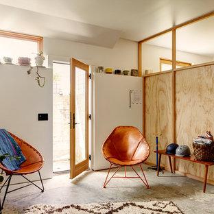Idée de décoration pour un sous-sol bohème avec béton au sol.