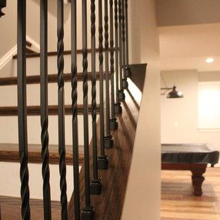 Aménagement d'un très grand sous-sol classique donnant sur l'extérieur avec un mur gris, un sol en bois brun, aucune cheminée et un sol marron.