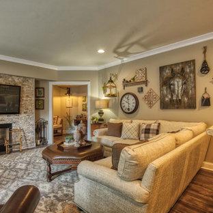 Idée de décoration pour un grand sous-sol champêtre donnant sur l'extérieur avec un mur beige, un sol en vinyl, un poêle à bois, un manteau de cheminée en pierre et un sol marron.