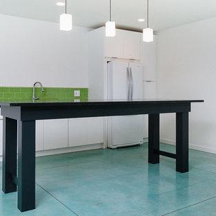 Cette photo montre un sous-sol tendance avec un mur blanc et béton au sol.