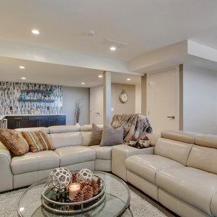 Cette photo montre un grand sous-sol chic donnant sur l'extérieur avec un bar de salon, un mur gris, un sol en bois clair, une cheminée standard, un manteau de cheminée en pierre de parement et un sol gris.