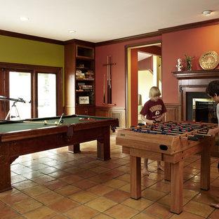 Idées déco pour un sous-sol classique donnant sur l'extérieur et de taille moyenne avec un mur rouge, un sol en carreau de terre cuite, une cheminée standard, un manteau de cheminée en bois et un sol orange.
