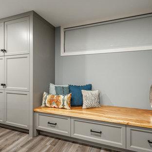 Aménagement d'un petit sous-sol craftsman semi-enterré avec un mur bleu, sol en stratifié, aucune cheminée et un sol gris.