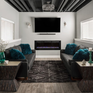 Basement - large transitional look-out gray floor basement idea in St Louis with gray walls and a ribbon fireplace