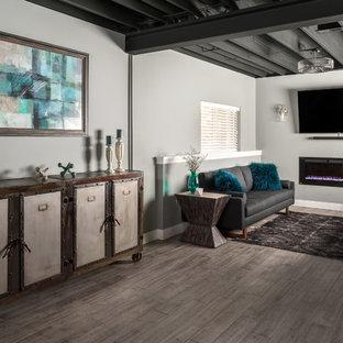 Cette photo montre un grand sous-sol chic semi-enterré avec un mur gris, un sol en carrelage de porcelaine, une cheminée ribbon et un sol gris.