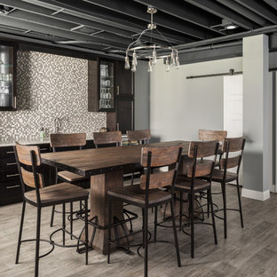 Example of a large transitional look-out gray floor basement design in St Louis with gray walls