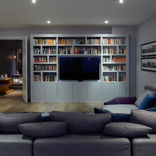 Medium sized contemporary fully buried basement in London with purple walls, medium hardwood flooring and no fireplace.