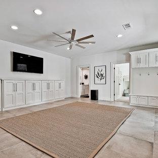 Cette image montre un grand sous-sol craftsman donnant sur l'extérieur avec un mur blanc, un sol en carrelage de porcelaine et un sol bleu.