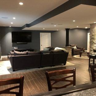 Idées déco pour un grand sous-sol moderne enterré avec un mur gris, un sol en carreau de terre cuite et un sol marron.