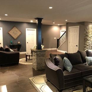 Foto på en stor funkis källare utan fönster, med grå väggar, klinkergolv i terrakotta och brunt golv