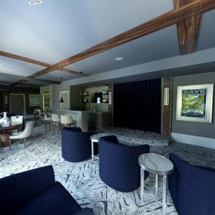 Cette image montre un grand sous-sol design donnant sur l'extérieur avec un bar de salon, un mur gris, moquette, une cheminée ribbon, un manteau de cheminée en pierre, un sol gris, un plafond en poutres apparentes et du papier peint.