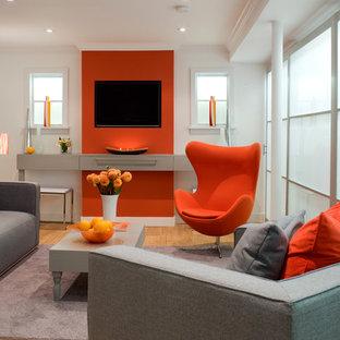 Cette photo montre un sous-sol tendance avec un mur orange et un sol en bois brun.