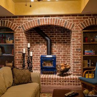 Réalisation d'un grand sous-sol chalet enterré avec un poêle à bois, un manteau de cheminée en brique, un mur jaune et un sol en bois foncé.