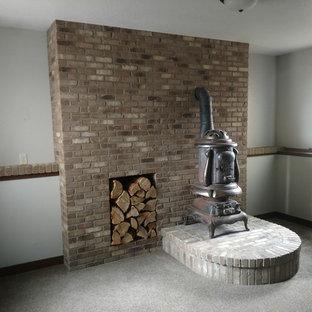 Cette photo montre un sous-sol craftsman semi-enterré et de taille moyenne avec un mur blanc, moquette, un poêle à bois, un manteau de cheminée en brique et un sol gris.