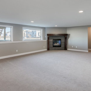 Example of a large trendy look-out carpeted basement design in Wichita with beige walls, a standard fireplace and a tile fireplace
