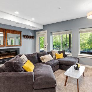 Cette photo montre un sous-sol chic donnant sur l'extérieur et de taille moyenne avec un mur gris, béton au sol, cheminée suspendue, un manteau de cheminée en métal et un sol bleu.