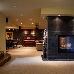 Cette image montre un grand sous-sol design donnant sur l'extérieur avec une cheminée double-face et un sol marron.