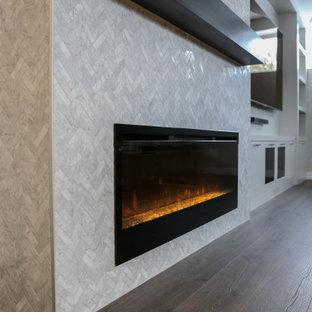 Cette photo montre un sous-sol tendance enterré avec un bar de salon, un mur blanc, un sol en bois brun, une cheminée standard, un manteau de cheminée en carrelage et du papier peint.