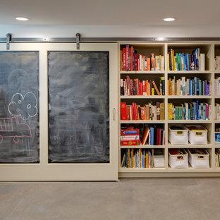 Aménagement d'un sous-sol contemporain avec un mur blanc, béton au sol et un sol gris.