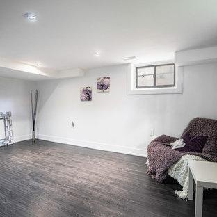 Idée de décoration pour un sous-sol minimaliste de taille moyenne avec un mur blanc et un sol en bois foncé.