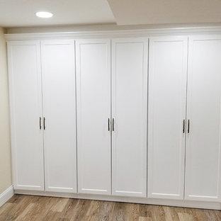 Modelo de sótano con puerta tradicional renovado, de tamaño medio, sin chimenea, con paredes blancas, suelo vinílico y suelo multicolor