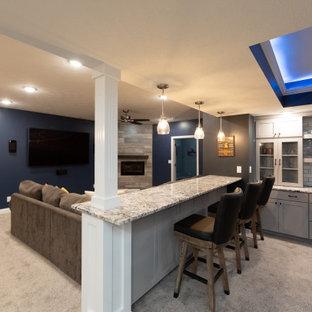 Idées déco pour un grand sous-sol contemporain semi-enterré avec un mur bleu, moquette, une cheminée standard, un manteau de cheminée en carrelage et un sol beige.