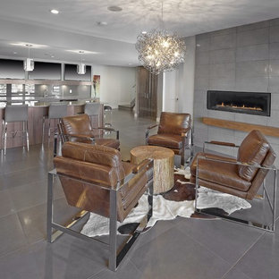 This is an example of an expansive contemporary basement in Edmonton with grey walls, a ribbon fireplace, a tile fireplace surround and ceramic floors.