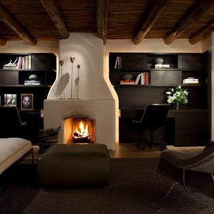 Idée de décoration pour un sous-sol méditerranéen enterré et de taille moyenne avec un mur beige, une cheminée standard et un manteau de cheminée en plâtre.