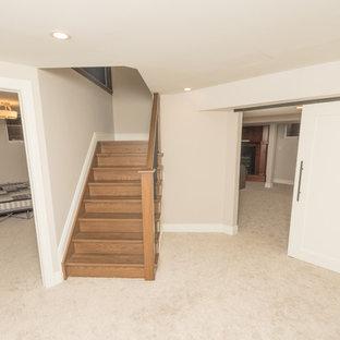 Aménagement d'un grand sous-sol classique enterré avec un mur blanc, moquette, une cheminée standard, un manteau de cheminée en bois et un sol beige.