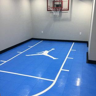 Réalisation d'un sous-sol design semi-enterré et de taille moyenne avec un mur gris, un sol en vinyl et un sol bleu.
