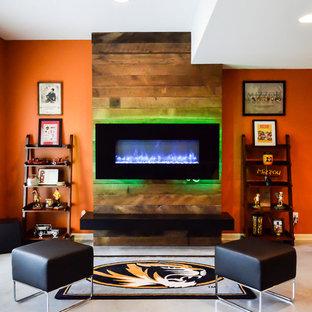 Cette photo montre un sous-sol moderne donnant sur l'extérieur et de taille moyenne avec un mur orange, béton au sol et une cheminée ribbon.