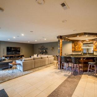 Cette image montre un grand sous-sol vintage donnant sur l'extérieur avec un mur gris, un sol en carrelage de céramique, aucune cheminée et un bar de salon.
