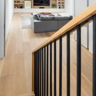 Photo of an expansive traditional fully buried basement in London with white walls, medium hardwood flooring and brown floors.