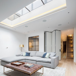 Inspiration for a medium sized contemporary fully buried basement in London with white walls, light hardwood flooring and beige floors.