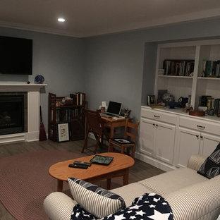 Idées déco pour un sous-sol classique enterré et de taille moyenne avec un mur gris, un sol en bois foncé, une cheminée standard, un manteau de cheminée en bois et un sol marron.