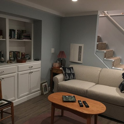 Example of a mid-sized classic underground dark wood floor and brown floor basement design in Boston with gray walls, a standard fireplace and a wood fireplace surround