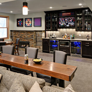 Inspiration for a mid-sized transitional walk-out carpeted basement remodel in Minneapolis with gray walls, a standard fireplace and a stone fireplace