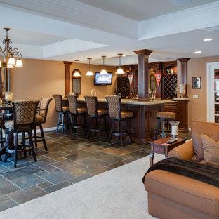 Cette image montre un grand sous-sol traditionnel semi-enterré avec un mur marron, un sol en ardoise, aucune cheminée et un bar de salon.