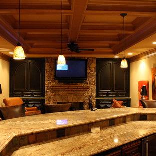 Aménagement d'un très grand sous-sol classique donnant sur l'extérieur avec un mur beige, un sol en bois foncé, un poêle à bois et un manteau de cheminée en pierre.