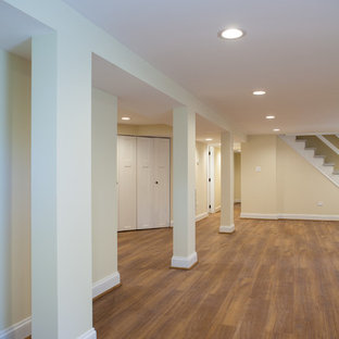 Réalisation d'un grand sous-sol tradition semi-enterré avec un mur beige et un sol en vinyl.