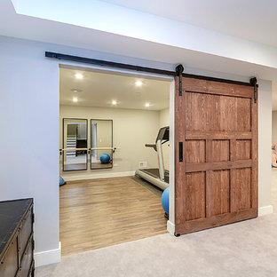 Diseño de sótano en el subsuelo de estilo americano, grande, con paredes grises y suelo de madera oscura