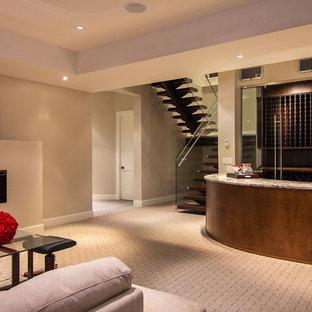 Réalisation d'un sous-sol design enterré avec un mur beige, moquette, une cheminée ribbon et un sol beige.