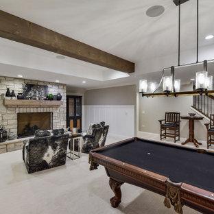 Exemple d'un grand sous-sol chic enterré avec un bar de salon, un mur blanc, moquette, une cheminée standard, un manteau de cheminée en pierre, un sol beige, un plafond en poutres apparentes et boiseries.